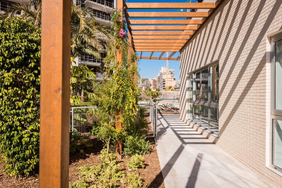 Porche de madera con jardín y vegetación en promoción residencial.
