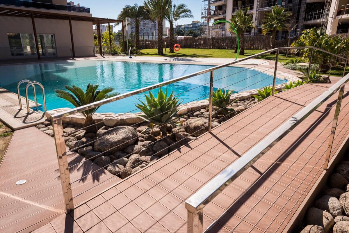 Piscina dividida por un puente con jardín y palmeras en promoción residencial Ítaca.