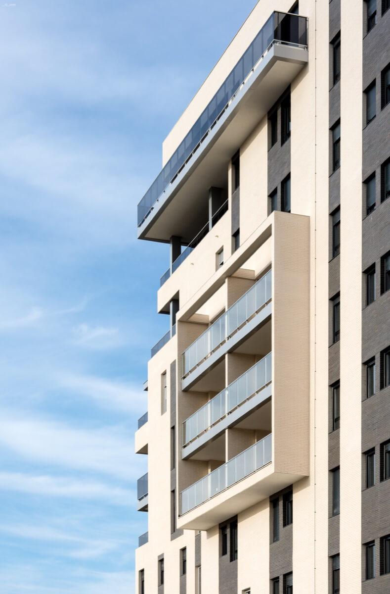 Detalle fachada ladrillo caravista blanco en promoción residencial.