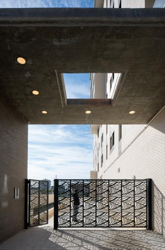 Portón de entrada del Residencial Ítaca, destaca el ladrillo caravista y la verja en formas uniformes.