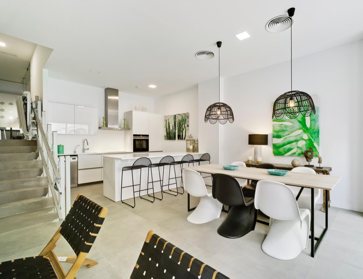 Fotografía interior del club social. Destacan la cocina, las mesas y las sillas en blanco y negro, junto a las luminarias de techo