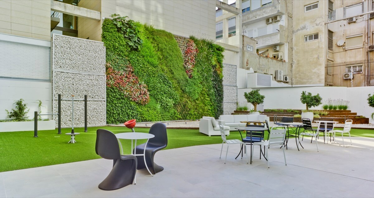 Fotografía general del patio comunitario del Edificio General Marvá 3. Destaca el jardín vertical, las mesas y las sillas para el descanso de los residentes.