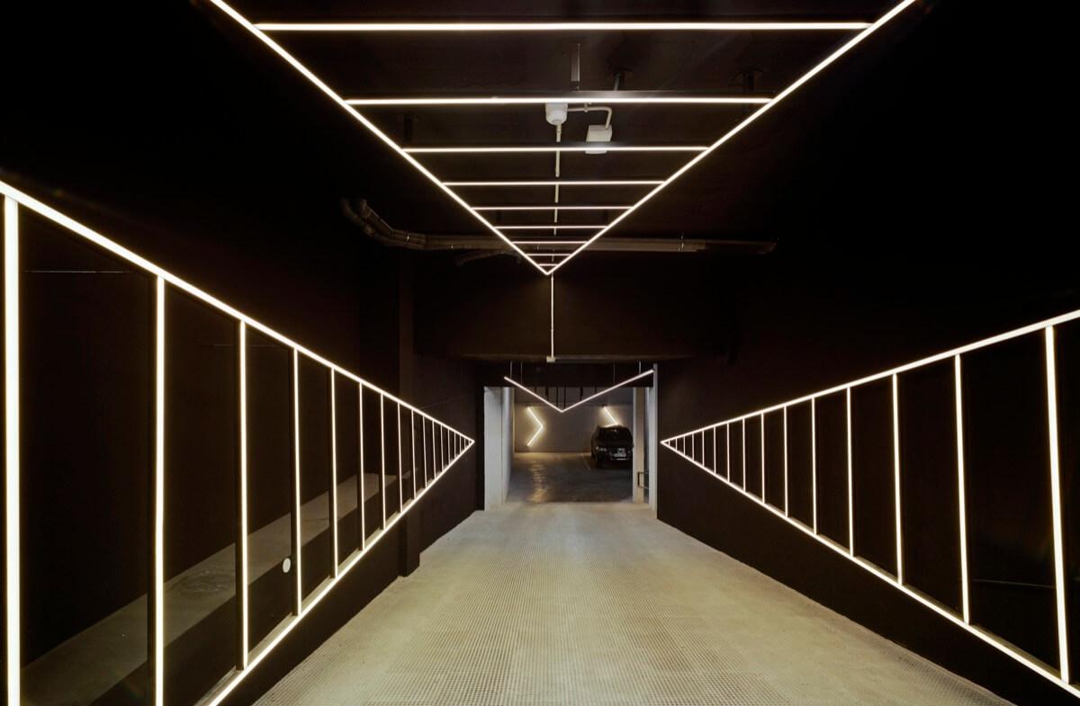 Fotografía de la entrada al garaje del Edificio General Marvá. Destaca el juego de luminarias led que acompaña durante la rampa