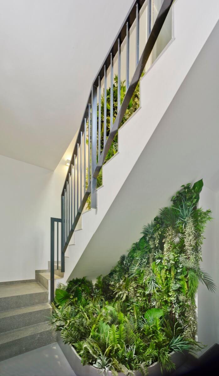 Escalera del garaje que conecta con la planta baja del Edificio General Marvá 3. Destaca la vegetación ubicada debajo de la escalera y sobre la pared.