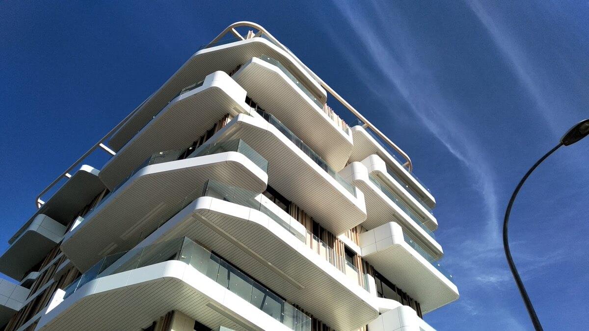 Fotografía contrapicada desde la calle de las terrazas del Residencial Nature by Kronos Homes. Destacan los anillos de aluminio blanco.