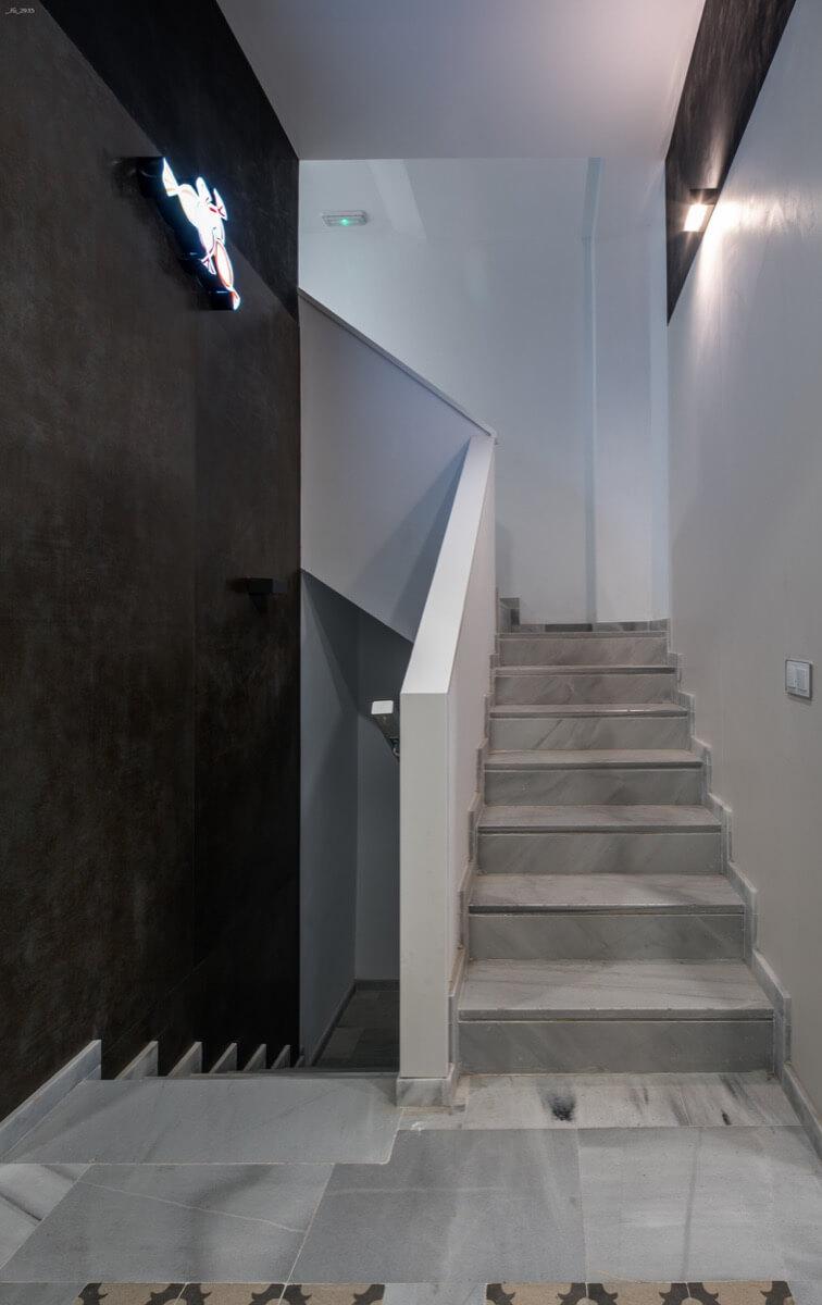 Escaleras de acceso a las plantas del Edificio Pintor Lorenzo Casanova. Destaca el pavimento con baldosas de hidráulicas y un luminoso de caramelos como guiño a la antigua tienda ubicada en el mismo lugar: Caramelos Picó.