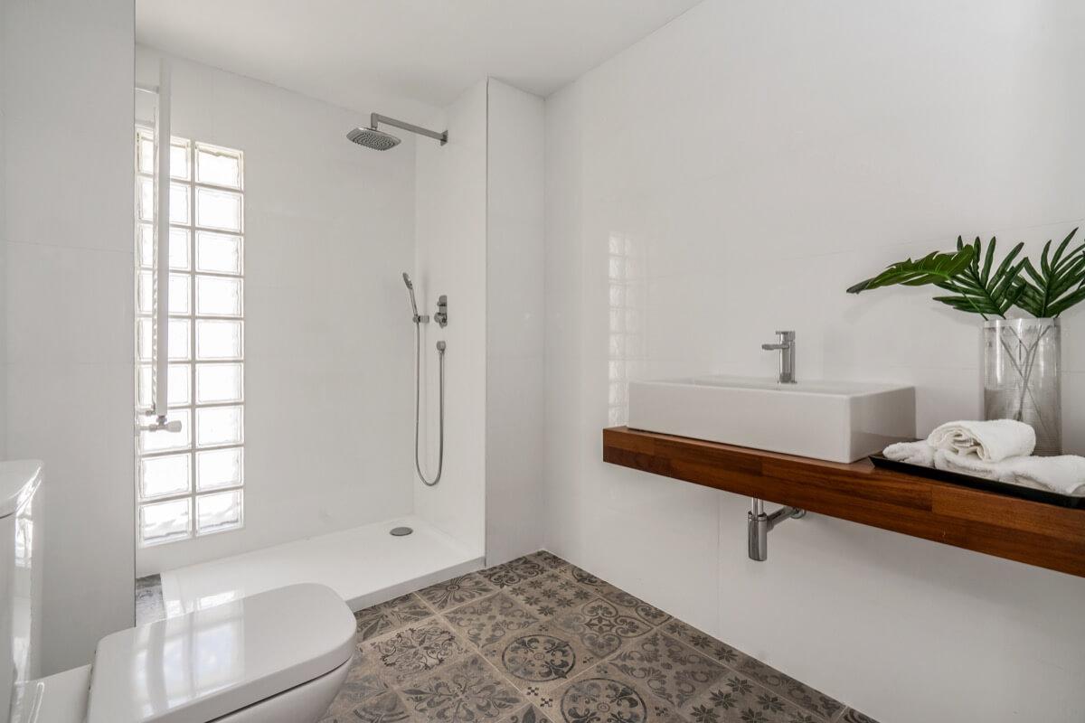 Fotografía interior cuarto de aseo en tonalidades blancas. Destaca la entrada de luz natural a través del pavés (ladrillo de vidrio) y el pavimento de baldosas hidráulicas