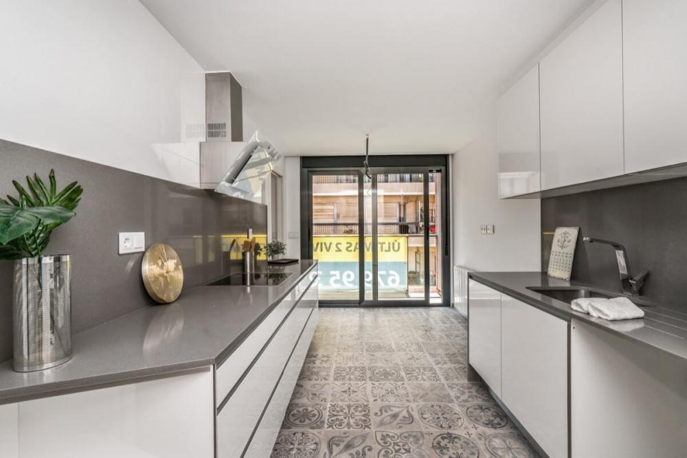 Fotografía interior de cocina del Edificio Pintor Lorenzo Casanova. Destaca el juego de tonalidades blancas y grises, la entrada de luz natural a través del ventanal y el pavimento de baldosas hidráulicas.