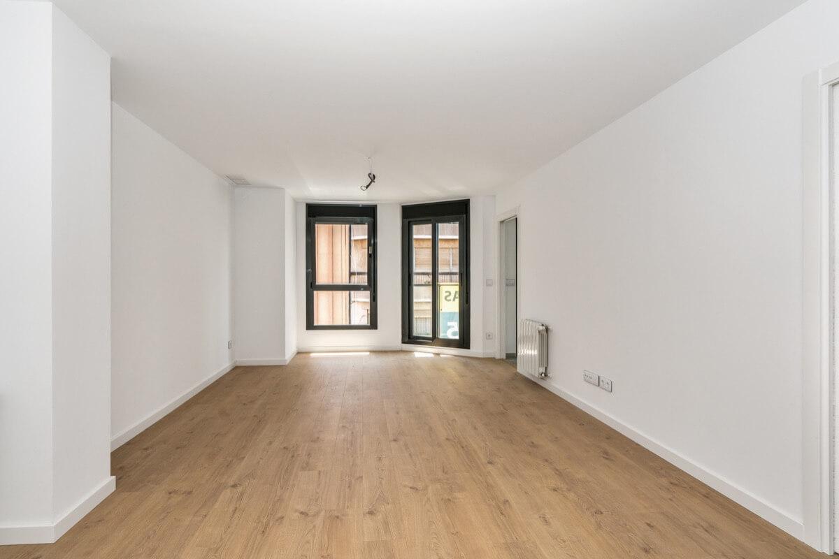 Fotografía interior de vivienda del Edificio Pintor Lorenzo Casanova. Destaca la entrada de luz natural por los ventanales, el pavimento laminado de madera y las tonalidades blancas de las paredes.