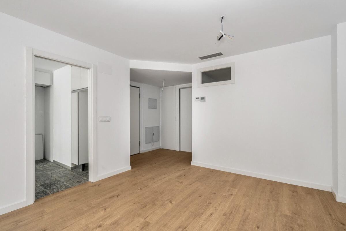 Fotografía interior de vivienda del Edificio Pintor Lorenzo Casanova. Destaca el suelo laminado de madera, las paredes en tonalidades blancas y el pavimento de baldosas hidráulicas del cuarto de baño.