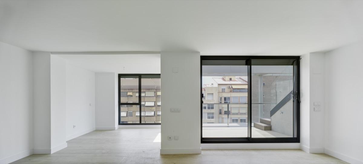 Fotografía interior del ático del Residencial Marvá. Destaca el color blanco y los grandes ventanales que dejan entrar la luz natural.