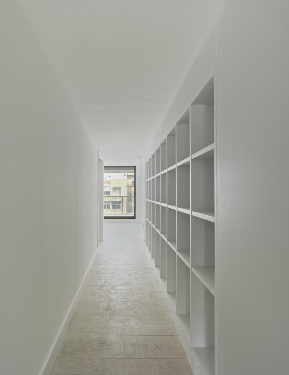 Fotografía interior del pasillo del ático. Destaca el color blanco y las estanterías cuadradas integradas en la pared.