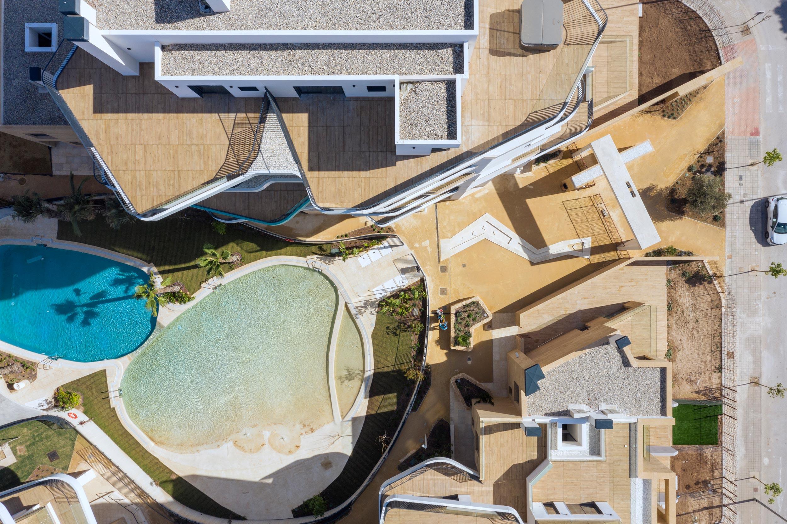 Vista aérea cenital desde dron de la piscina tipo playa y urbanización de Allonbay Village