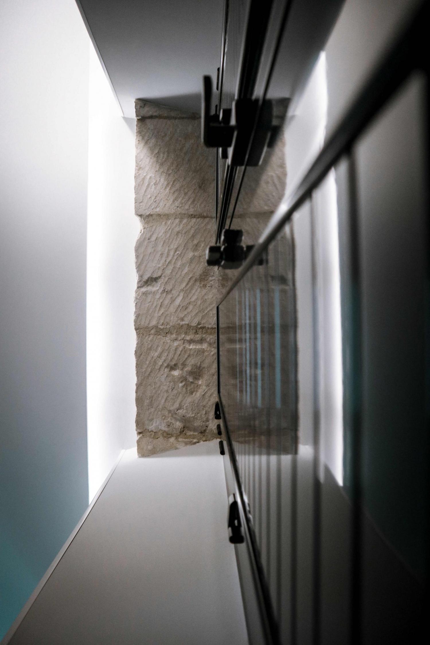 Vista picada de los muros de piedra sobre los ventanales de las viviendas de Labradores 24