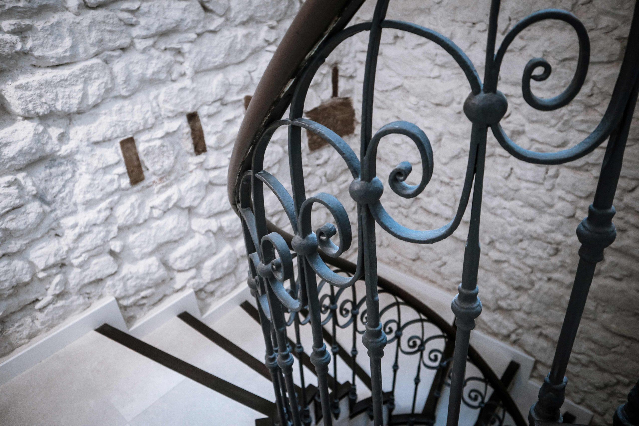 Vista detalle escalera helicoidal de Labradores 24 con el muro de piedra en el fondo