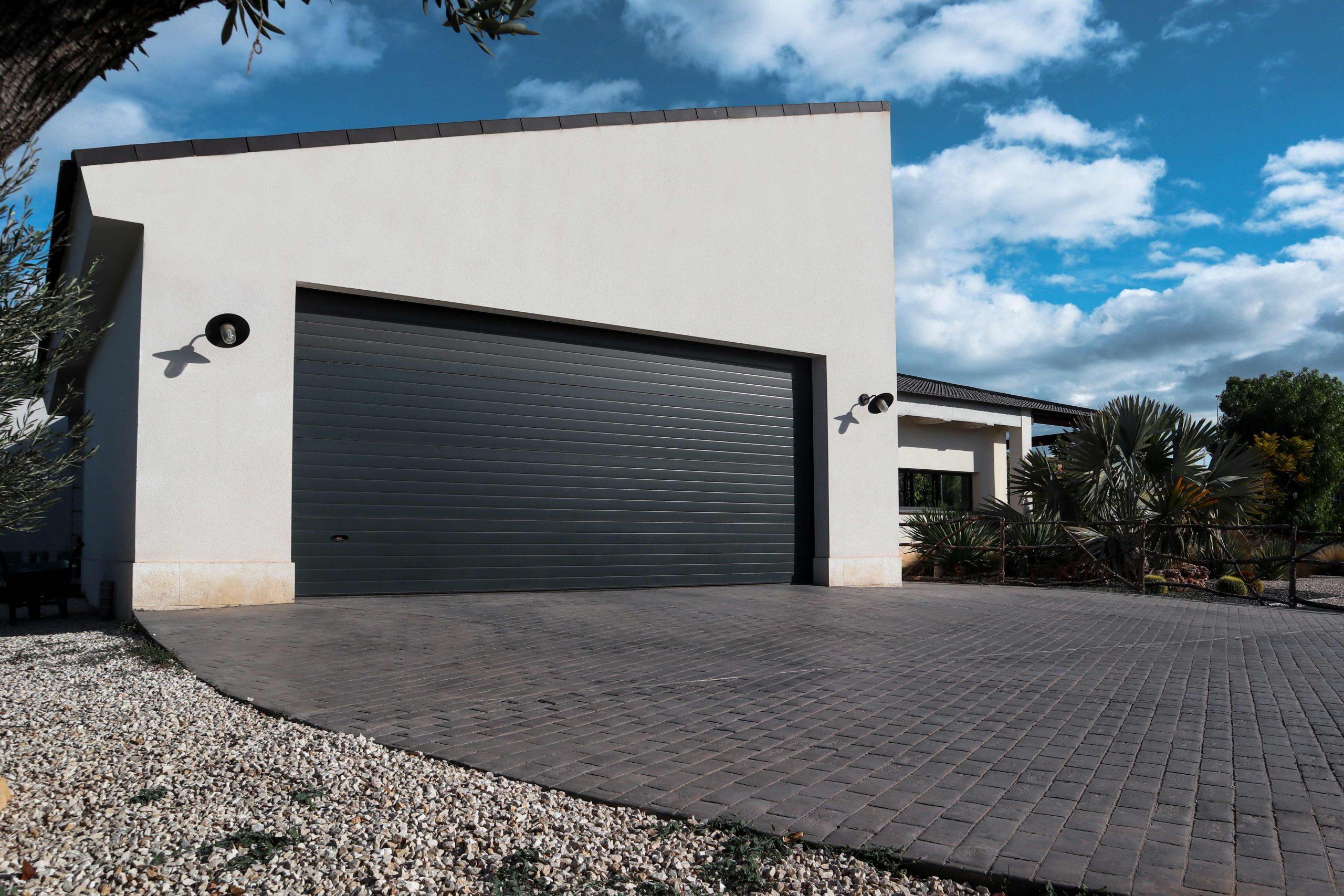 Puerta del garaje de Villa ADE, rampa de entrada y jardín cercado con valla de madera rústica al fondo.