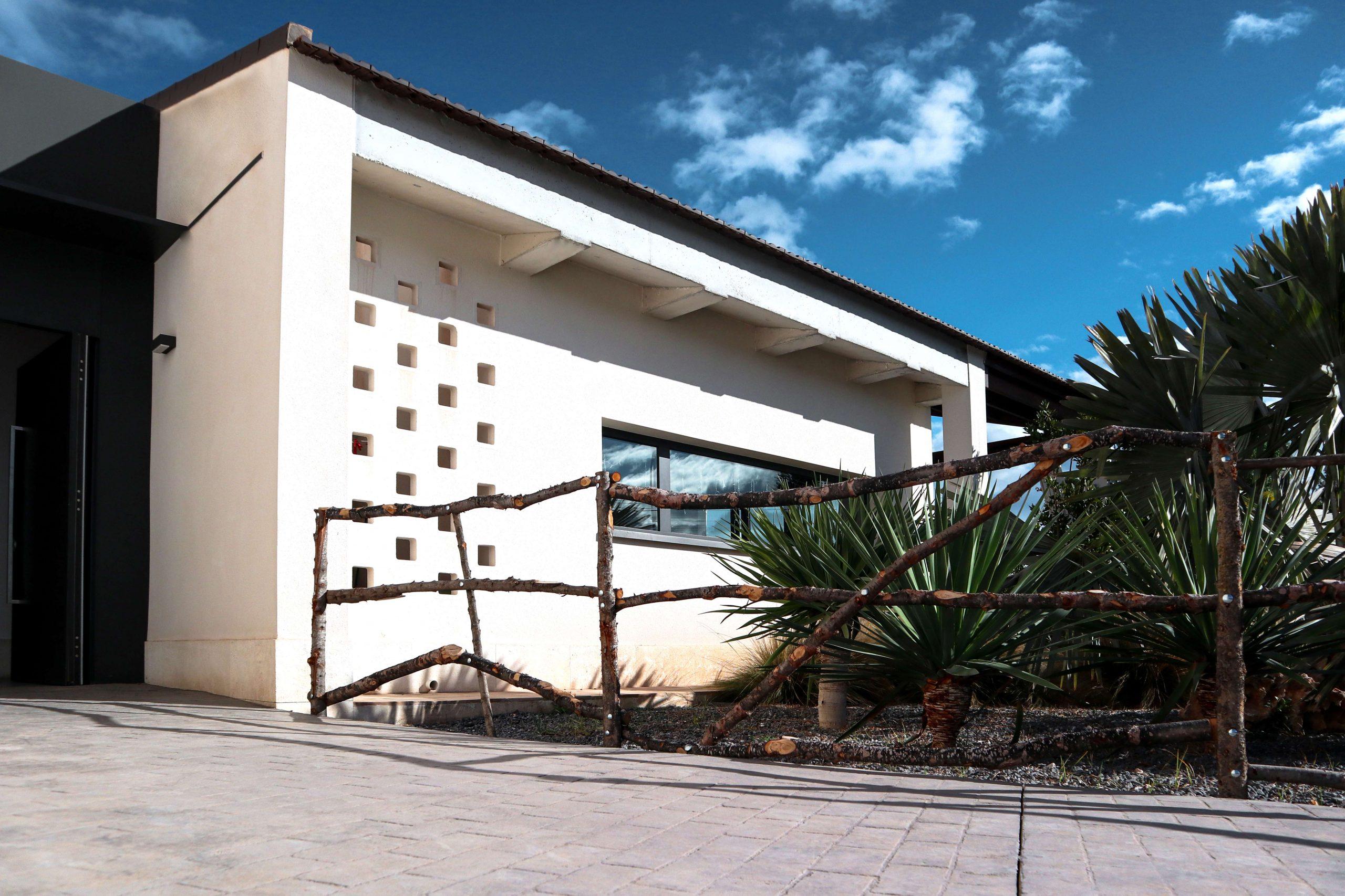 Fachada vivienda unifamiliar y jardín cercado con valla de madera rústica, arquitectura unifamiliar