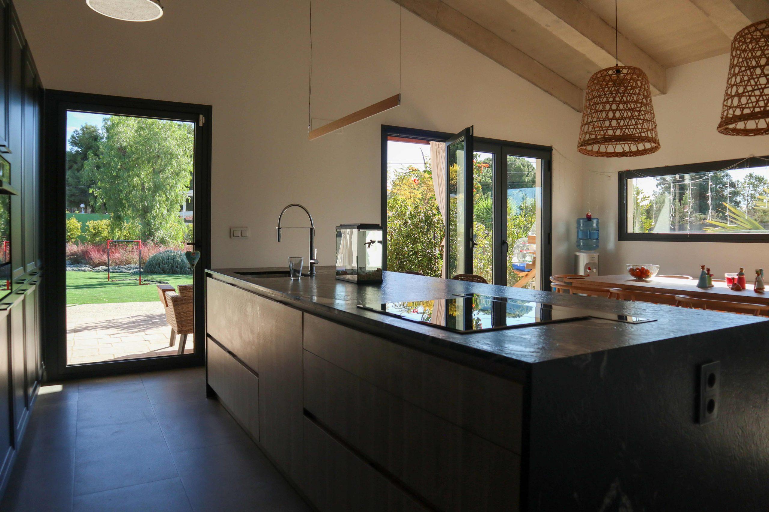 Isla de cocina con luminarias colgantes de techo y mesa de madera para comedor