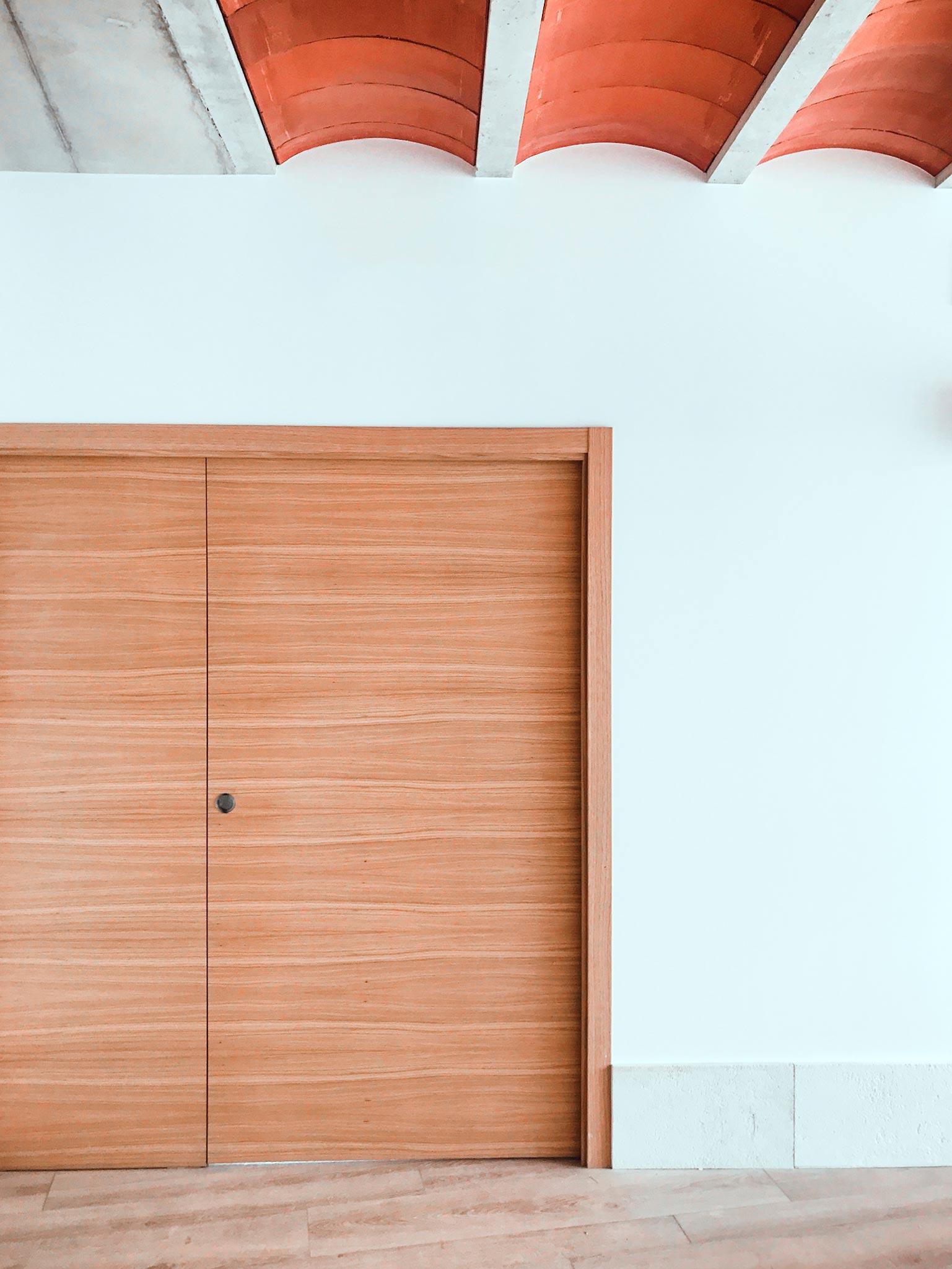 Salón moderno con puerta corredera de madera y techo de bovedillas cerámicas.