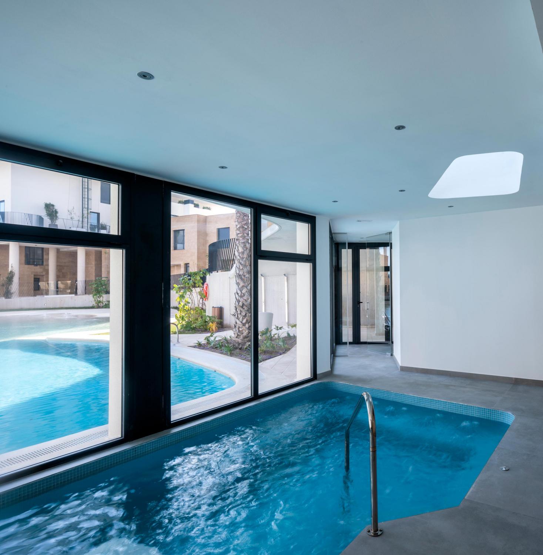 Interior spa de Allonbay Village con vistas a la piscina tipo playa gracias al gran ventanal que conecta las zonas de agua. Destaca el lucernario que permite la entrada luz natural.