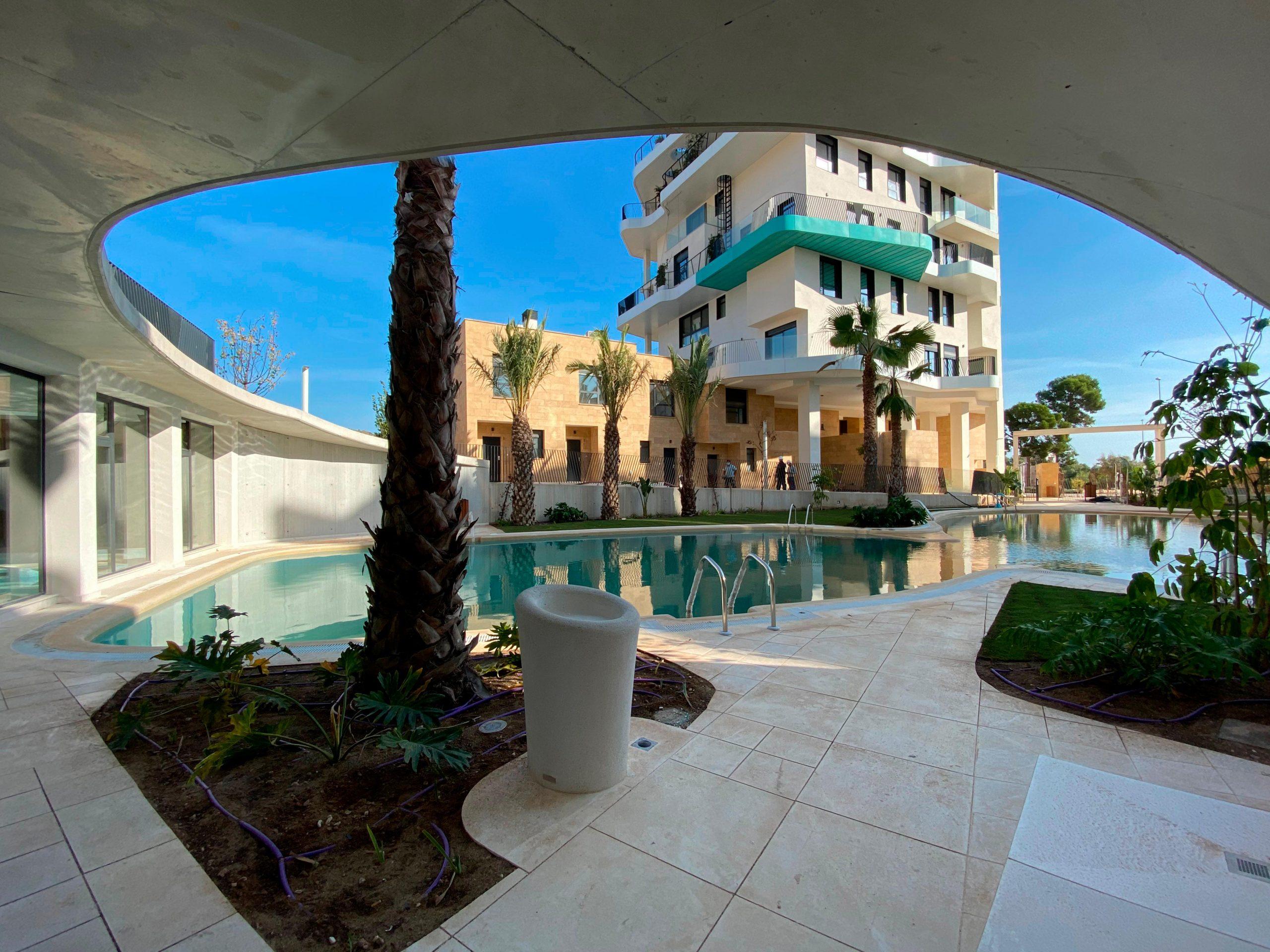 Visera de spa. Vistas a la torre de Allonbay Village, piscina tipo playa y vegetación de la urbanización
