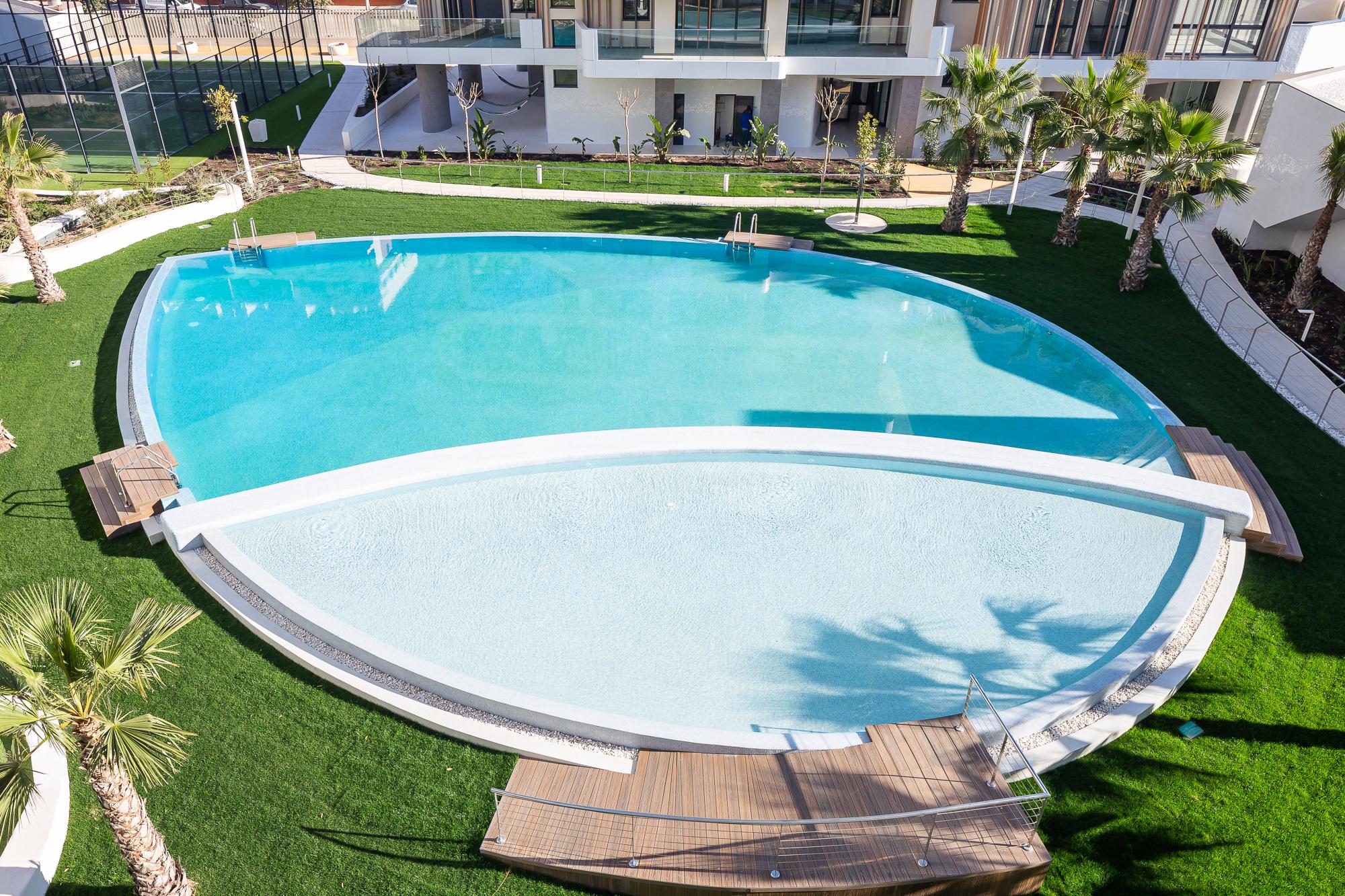 Zona de piscina en forma de gota rodeada de césped. Residencial Nature by Kronos Homes