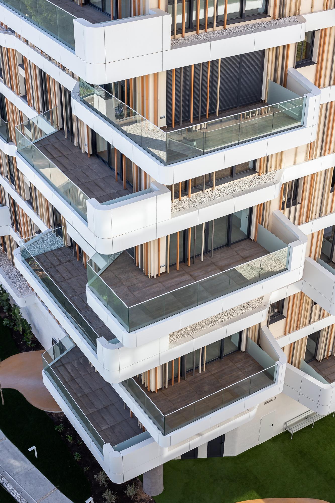 Fotografía detalle en vista picada de las terrazas del Residencial Nature By Kronos Homes. Destacan las terrazas uniformes, las lamas cerámicas y los anillos de aluminio blanco.
