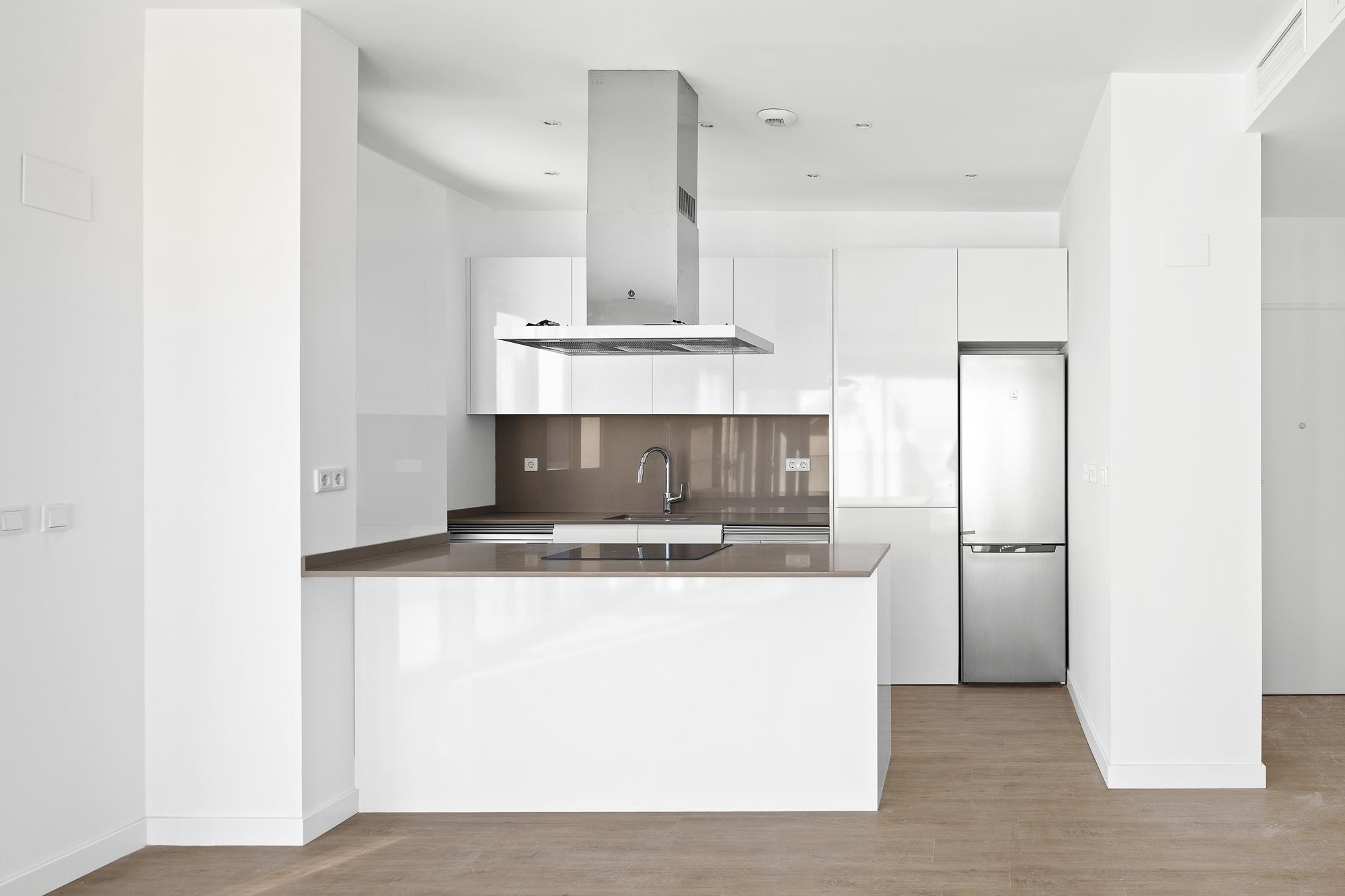 Fotografía frontal de cocina blanca abierta en Residencial Nature.