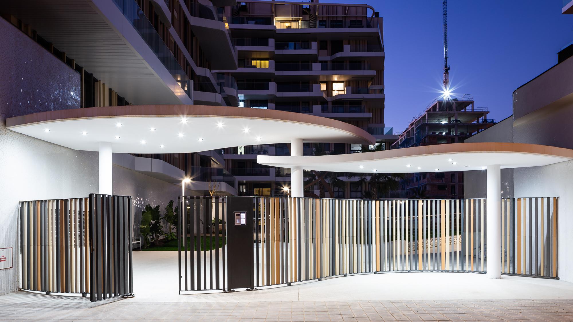 Entrada del residencial Nature en forma curvilínea con lamas cerámicas, iluminación y videoportero.