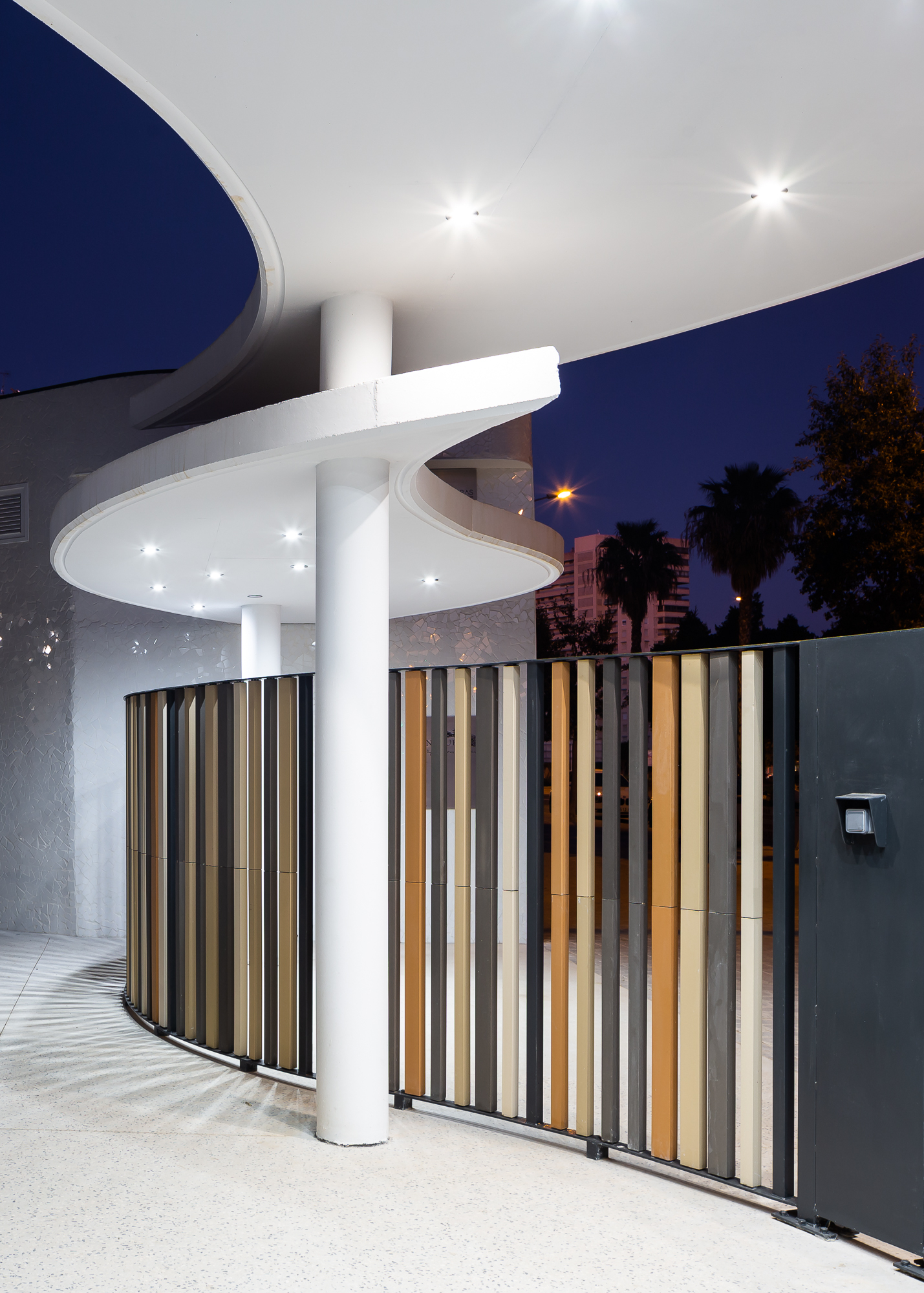 Entrada del residencial Nature by Kronos Homes en forma curvilínea con lamas cerámicas e iluminación.