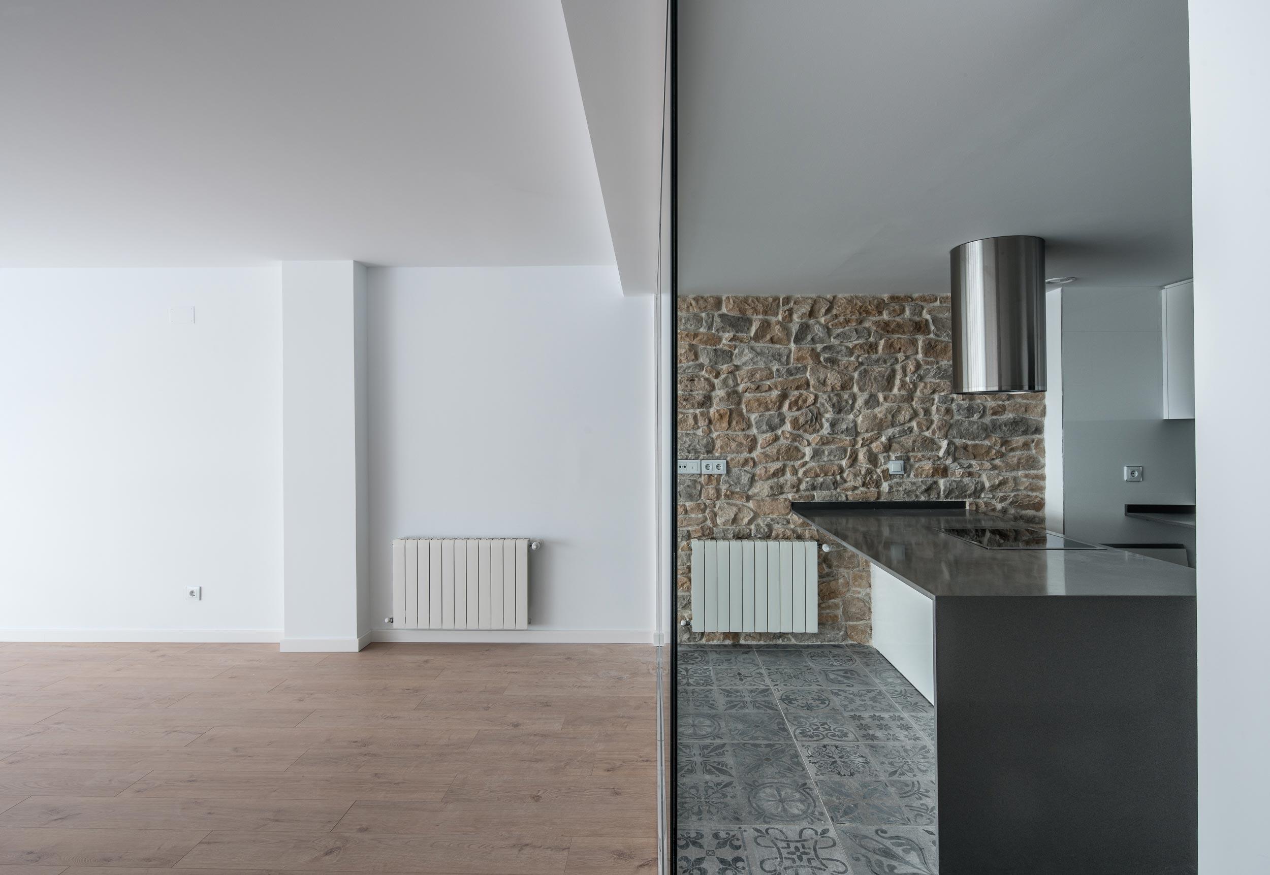 Fotografía frontal interior de la cocina y salón separados mediante una cristalera que conecta visualmente ambas zonas. Destaca el muro de mampostería de la cocina. Pintor Lorenzo Casanova.