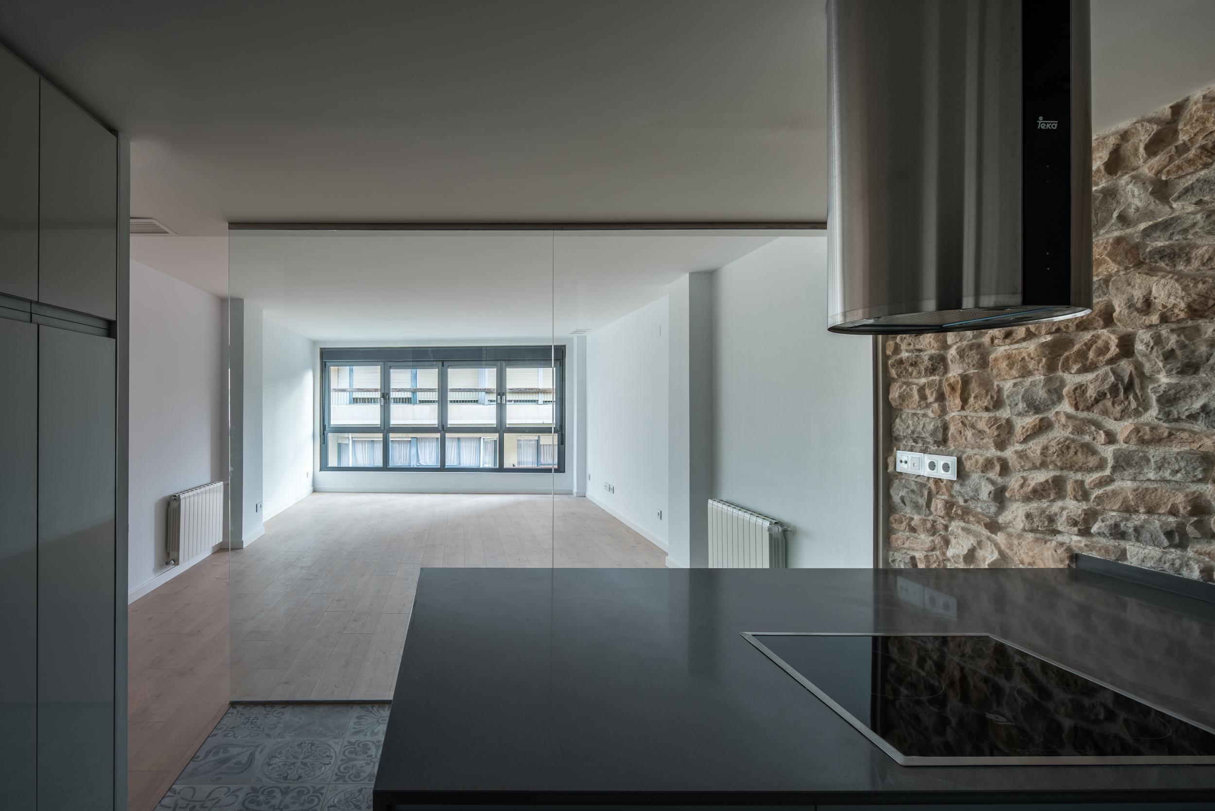 Fotografía interior desde la cocina de Pintor Lorenzo Casanova hacia el salón. Ambas zonas quedan conectadas visualmente gracias a una gran cristalera que separa ambas estancias. Destaca el muro de mampostería y la campana extractora de humos para cocina.
