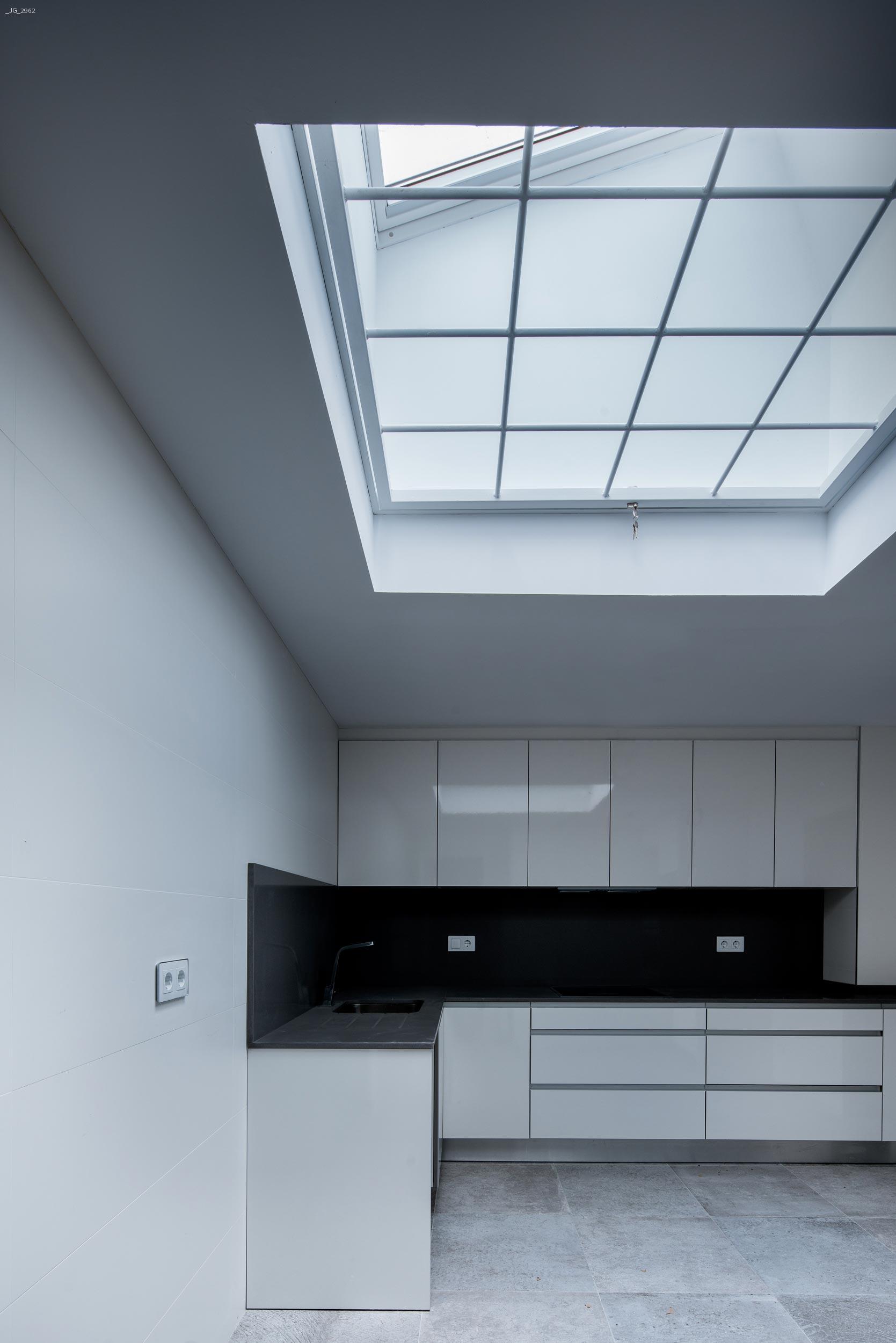 Ventana de techo en moderna cocina blanca.